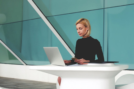 female lawyer: Confident businesswoman holding mobile phone while checking email on laptop computer, intelligent female lawyer with cell telephone in hand keyboarding important document for lawsuit via net-book