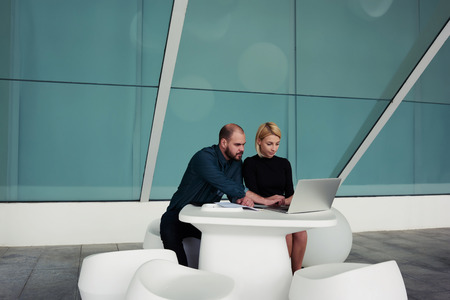 ceos: Young man and woman reading comments from clients about their new project through net-work on laptop computer, team of creative designers working together on net-book while sitting in office interior