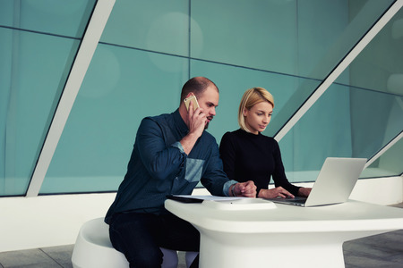 ceos: Young businessman talking on mobile phone with client while his secretary keyboarding on net-book, male and female economists using cell telephone and laptop computer while working together in office