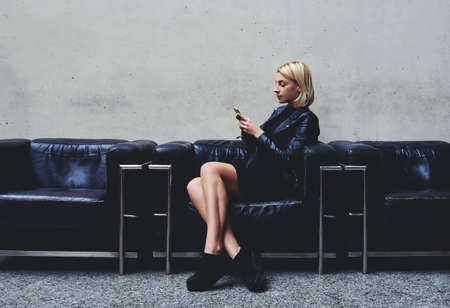 prettiness: Stylish hipster girl chatting on mobile smart phone with her friend which she awaits before a photo session in the fashion studio, young blonde woman reviewing traffic in Internet via cell telephone