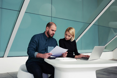 ceos: Two professional economists using paper documents and laptop computer for checking monthly report, man and woman entrepreneurs working together on portable net-book in modern office interior