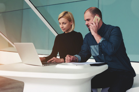 ceos: Man calling with mobile phone while his assistant searching needed information on laptop computer, two confident business workers using net-book and cell telephone for the development of joint project