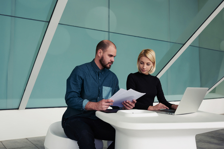 ceos: Successful business people checks monthly income on paper documents and laptop computer while sitting in office space, man and woman professional bookkeepers working together with reports and net-book