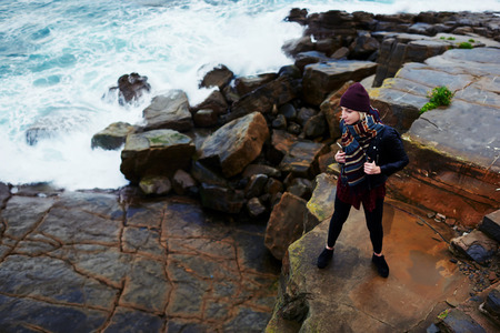 admires: Young female traveler with mobile phone in hand enjoying the sound of sea waves while standing on stone coast in autumn day, stylish woman holding cell telephone while admires beautiful ocean view