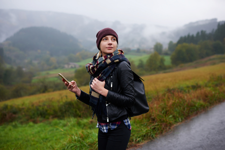 Trendy woman catches signal on her mobile phone while searching interesting places in mountains, beautiful female tourist with rucksack waiting for a text message on cell telephone during walking tour
