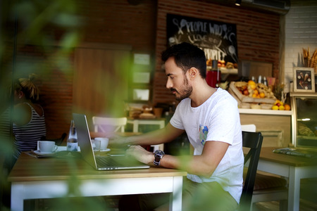 comfortable: Man owner of the organic shop making a monthly sales report on net-book while sitting at table indoors, young handsome male resting after work on laptop computer in comfortable modern coffee shop