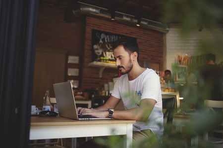 Experienced male freelancer connecting to wireless via net-book during lunch break in comfortable coffee shop interior, small business owner developing new menu on laptop computer for his cozy cafe