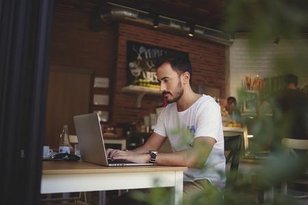 Tapasztalt férfi szabadúszó csatlakozó vezeték útján nettó könyv ebédszünet alatt a kényelmes kávézóban belső, kis üzlet tulajdonosa fejlődő új menü laptop az ő hangulatos kávézó