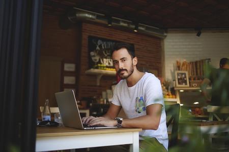 negocios comida: desarrollador hombre joven que crea el sitio web en el ordenador portátil mientras está sentado en la moderna cafetería interior, exitoso teclado dueño del negocio en la red-libro mientras se trabaja para su propio pequeño café en interiores