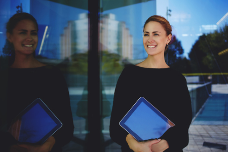 expects: Young woman professional realtor smiling for her clients which she expects outdoors near modern building, cheerful female skilled manager holding digital tablet while standing outside of big company