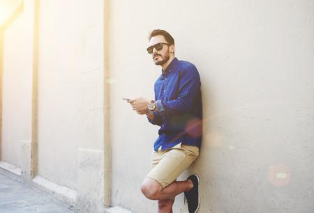 hombre de la barba confía en la celebración y el teléfono móvil mientras está de pie cerca de la pared de la calle en la tarde de verano soleado, chico joven inconformista de moda que usa el teléfono celular mientras se presenta al aire libre cerca del área de espacio de la copia