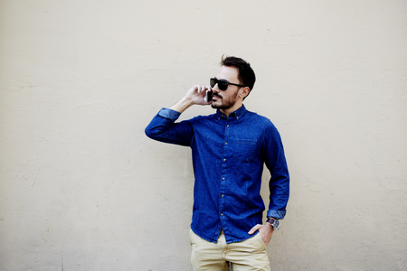 modern man: Half length portrait of stylish hipster guy talk with friend via mobile smart phone while strolling outdoors,bearded man calling with cell phone while standing against street wall with copy space area