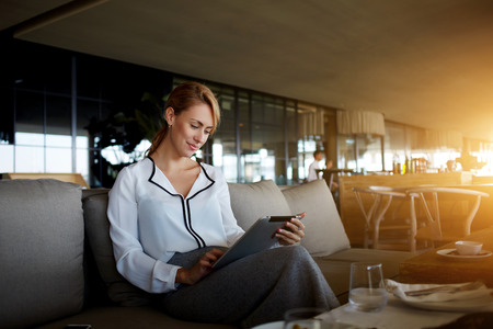 Pretty young female searching information on digital tablet while waiting for her friend in modern cafe interior,elegant businesswoman using touch pad while reading femenine blog of fashion and health