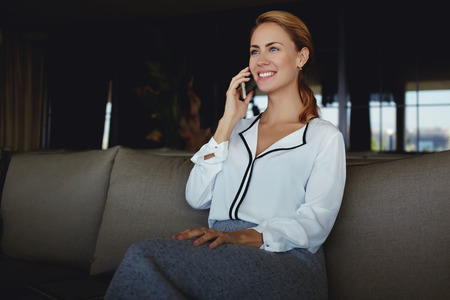 Happy young female talking on mobile phone while enjoying rest in modern interior after hard work day,successful businesswoman having nice conversation with boss via cell telephone before presentation