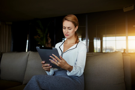 electronic book: Young confident businesswoman viewing news on touch pad while sitting in modern hotel interior, attractive elegant female read electronic book on digital tablet while waiting for orders in restaurant Stock Photo