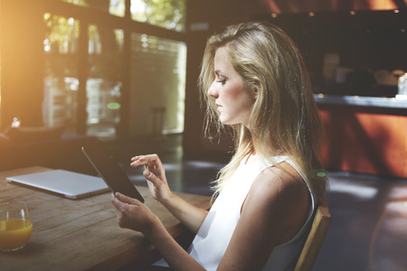 gente trabajando: Mujer busca la información necesaria en la red a través de la almohadilla táctil mientras se está sentado a la mesa con libros en red cerrada de co-working café, la joven charlar con los amigos en la superficie táctil mientras se relaja en la barra de