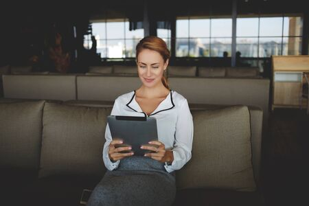 watching movie: Woman reading required information on portable touch pad while waiting for the beginning of the interview, female owner reviews the monthly report on digital tablet while sitting in her restaurant