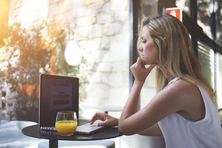 Attractive hipster girl searching friends in social network via laptop computer during recreation time, nice young woman ordering clothes in internet via net-book while sitting in favorite modern cafe