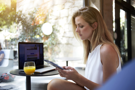 ecomerce: Young focused woman reading news on mobile phone while sitting with open net-book in cafe, female freelancer watching video on cell telephone during break after creating website on laptop computer