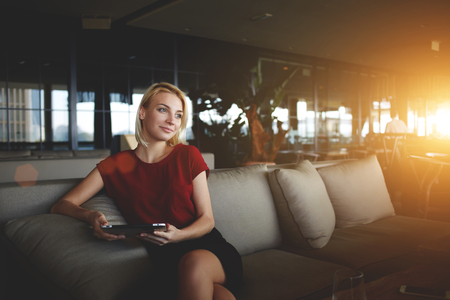 restaurateur: Intelligent businesswoman holding touch pad and dreaming about growth her career while resting in cafe,young female manager waiting for e-mail on digital tablet while sitting in modern office interior