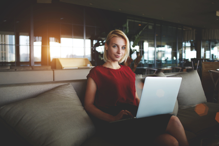 restaurateur: Successful female restaurateur with laptop computer waiting for business partners while sitting in office interior, young woman employer posing during work on net-book in modern comfortable cafe Stock Photo