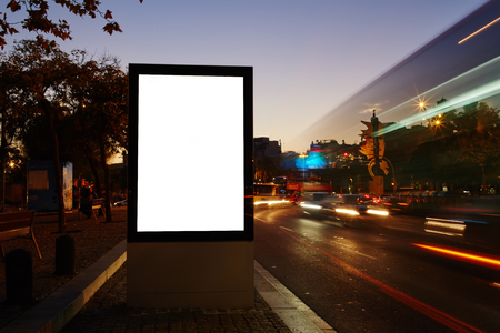 lightbox: Illuminated blank billboard with copy space for advertising message or content, information board Lightbox with night city on background, promotional mock up in urban scene, empty poster on roadside