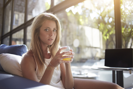 sweden resting: Attractive blonde hair woman posing while drinking a glass of fresh orange juice after work on net-book, pretty young female enjoying vitamin beverage while sitting in home near open laptop computer Stock Photo