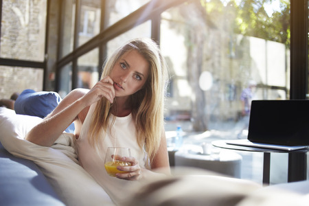 sweden resting: Pretty blonde hair woman posing with glass of orange juice while sitting in modern interior near table with open net-book, charming young female holding cocktail in hand while enjoying rest in cafe