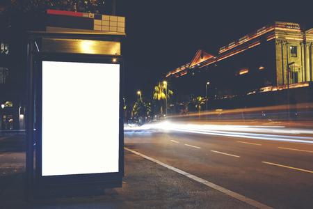 Elektronisch leeg aanplakbord met exemplaarruimte voor uw reclametekstbericht of inhoud, openbaar informatiebord in nachtstad, promotiemodel omhoog in stedelijke scène, lege Lightbox in metropolitaanse stad