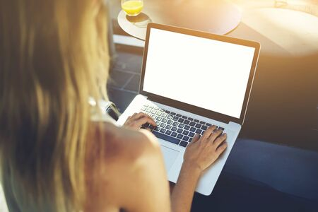 space for type: Closeup image of young hipster girl keyboarding on portable net-book with blank copy space screen for your advertising content, woman type message on laptop computer while relaxing in cozy coffee shop Stock Photo