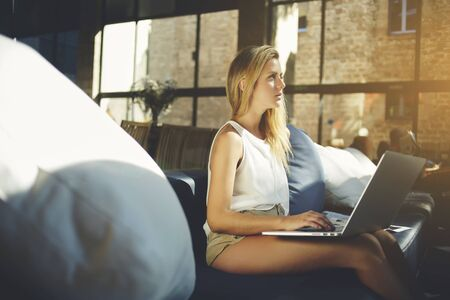 netbook: Thoughtful young female blogger holding open laptop computer on knees while sitting in co-working cafe, pretty hipster girl looking away while waiting answer in social network on portable net-book