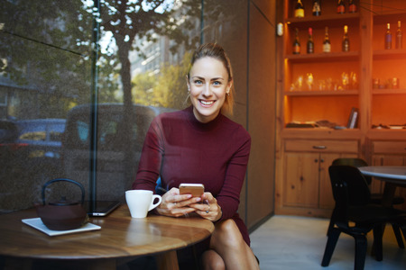 european people: Young woman with beautiful smile posing while sitting with smart phone in modern coffee shop interior, gorgeous cheerful female waiting for a call on her cell telephone during rest in cozy cafe bar Stock Photo
