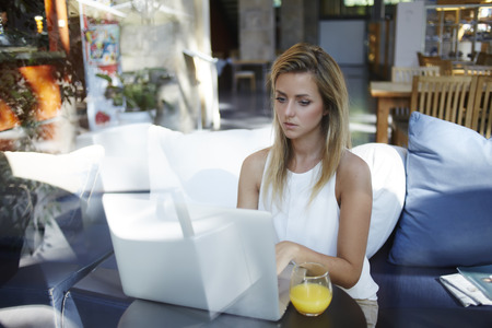 coursework: Young woman keyboarding on laptop computer while sitting in comfortable coffee shop during breakfast, charming female international student preparing coursework on net-book before exam at University Stock Photo