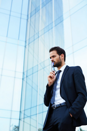 financier: Man millionaire dressed in luxury suit having rest before meeting with potential buyers shares of his company, confident male financier having work break while standing outdoors against skyscraper Stock Photo