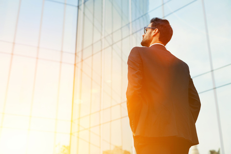 company building: Back view of rich businessman with hands in pockets looking on his skyscraper building while standing outside, young confident male manager dreaming about growth his career during work break outdoors Stock Photo