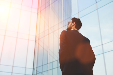 hombre barba: Vista posterior del hombre de negocios seus en los vidrios del ojo que mira en el espacio de la copia de pie sobre rascacielos de cristal, joven empleado profesional a la espera de los socios internacionales aire libre cerca de gran empresa