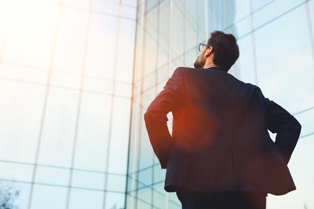 Vista posterior del arquitecto de sexo masculino que mira en el diseñado por él edificio de un banco moderno, mientras que fuera de pie, joven hombre de negocios inteligente soñando con la prosperidad de su empresa después de importante reunión