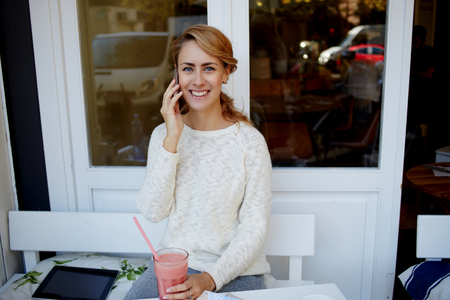 sidewalk talk: Happy woman having pleasant conversation on mobile phone during lunch break in modern coffee shop, cute female with beautiful smile talking on cell telephone while enjoying juice in sidewalk cafe
