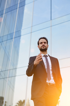 conclude: Serious male entrepreneur with arm extended for a handshake standing outdoors near modern office building, young man banker dressed in luxury suit offer his hand to conclude deal while walking outside