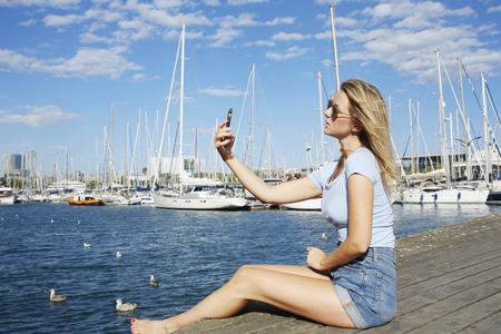 network port: Female wandered making photo with mobile phone camera while sitting on the wooden pier near sea port, woman photographing herself on cell telephone for social network pictures while relaxing outdoors
