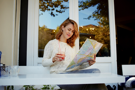 prettiness: Attractive woman resting in sidewalk cafe and searching locations on city map during her spring vacation, young female tourist exploring atlas while drinking juice and relaxing in modern coffee shop