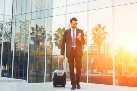エレガントなビジネスマンのスーツケース空港、タクシー車の屋外仕事の旅行の前に待っている間携帯電話を使用して経験豊富な男性の雇用者外で 写真素材