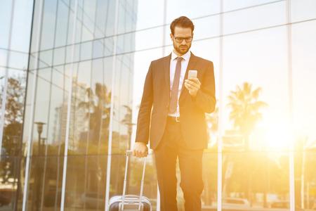 Junge männliche CEO mit Koffer Textnachricht auf Mobiltelefon zu lesen, während im Freien zu Fuß in der Nähe von Gebäude mit Stadt Reflexion, intelligent Arbeitgeber wählt die Nummer auf Smartphone vor Geschäftsreise