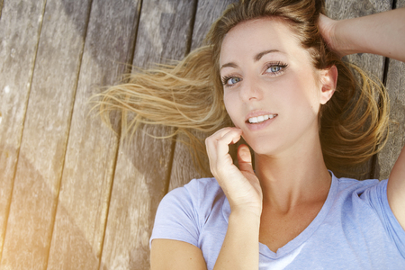prettiness: Closely image of a young Sweden model posing for creating a new portfolio for fashion photo agency, charming blonde female with natural beauty looking at camera while lying on a wooden background