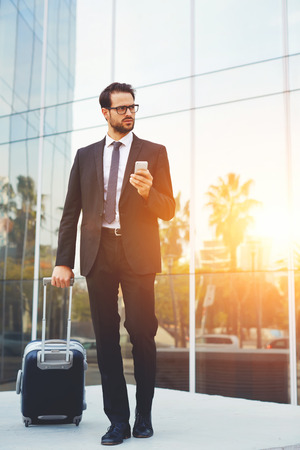 expects: Young confident man entrepreneur holding mobile phone and looks at the taxi that he expects with suitcase outdoors, serious male CEO waiting for a call on cell telephone before his business trip