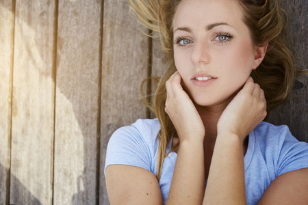 feminine beauty: Closely image of a young gorgeous woman with beautiful blue eyes posing while lying on a wooden background with copy space, attractive Sweden female looking at camera, feminine beauty concept