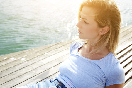 sweden resting: Closeup image of a young woman tourist thinking about her amazing summer adventure while relaxing near sea, attractive female wandered enjoying beautiful view while lying on a wooden jetty near lake