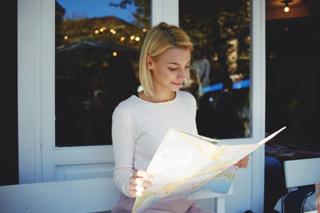 prettiness: Charming hipster girl examines geographical atlas while sitting in modern sidewalk cafe in summer day, young woman traveler searching locations on city map while enjoying rest in cozy coffee shop