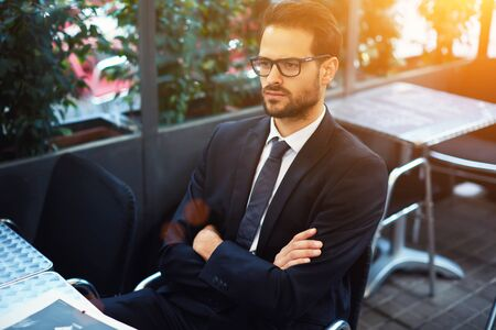 expects: Young serious man employer in glasses waiting for start interview while sitting in comfortable restaurant interior, male confident CEO expects a partners to sign an agreement on further cooperation