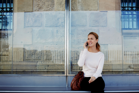women talking: Young beautiful woman talking on mobile phone while waiting public transportation at urban setting station, smiling female having pleasant conversation on cell telephone while sitting on a bus stop